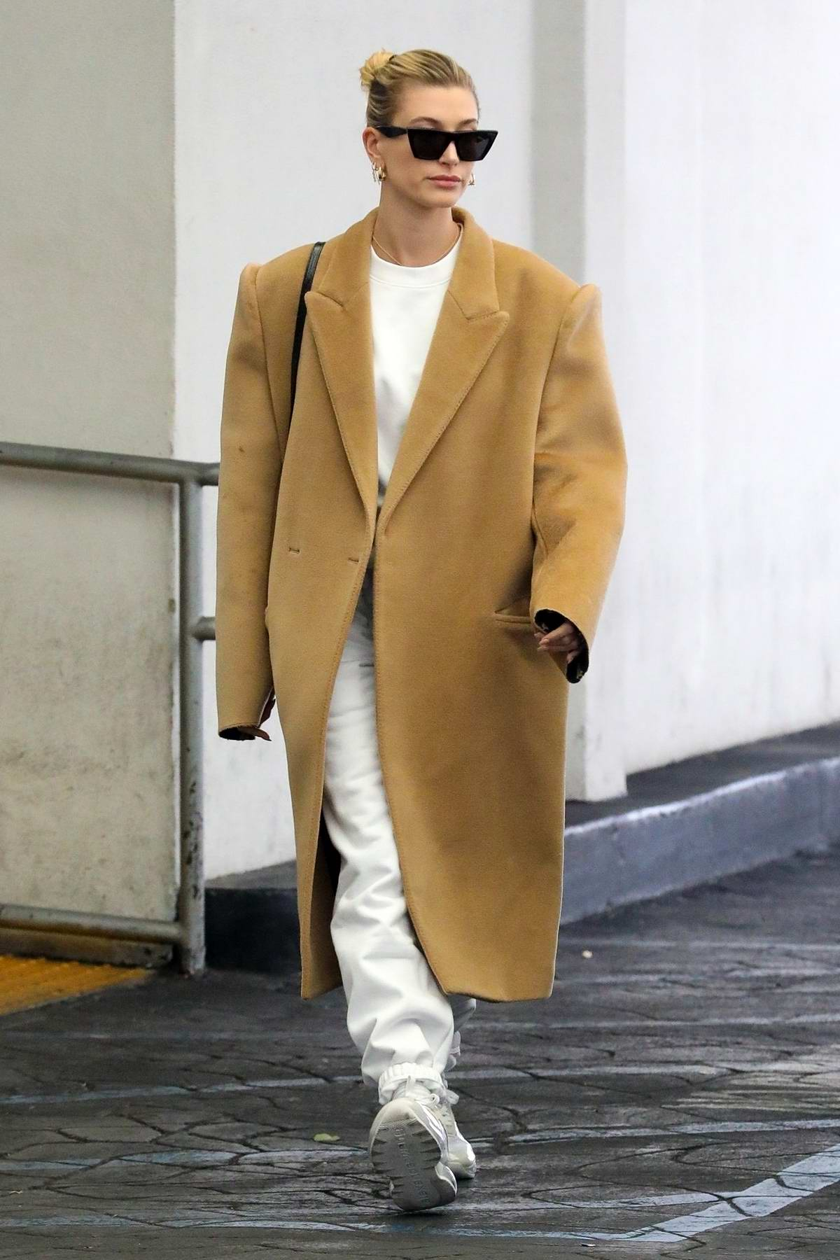 Hailey Bieber wears an oversized beige coat as she makes a visit to a doctor's office in Beverly Hills, Los Angeles