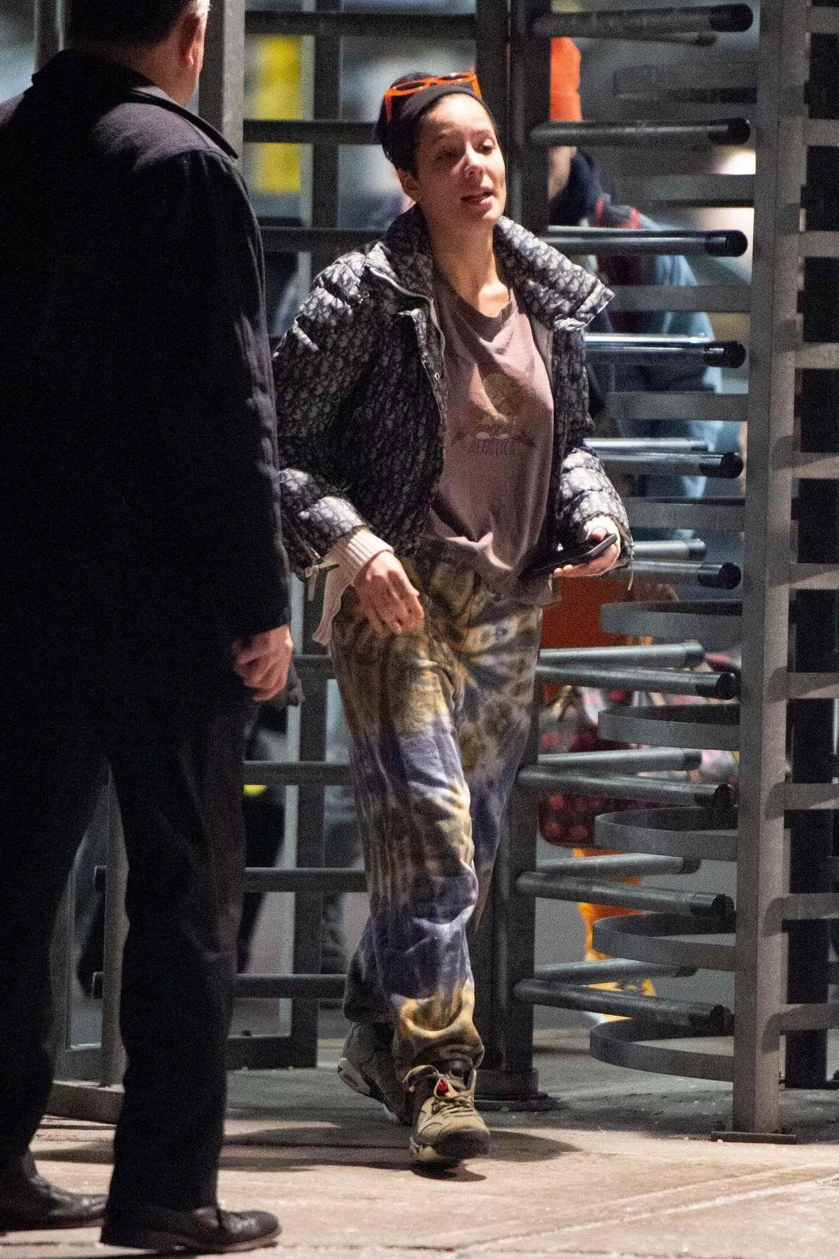 Halsey wears tie-dye sweatpants as she and Evan Peters arrive at JFK Airport in New York City