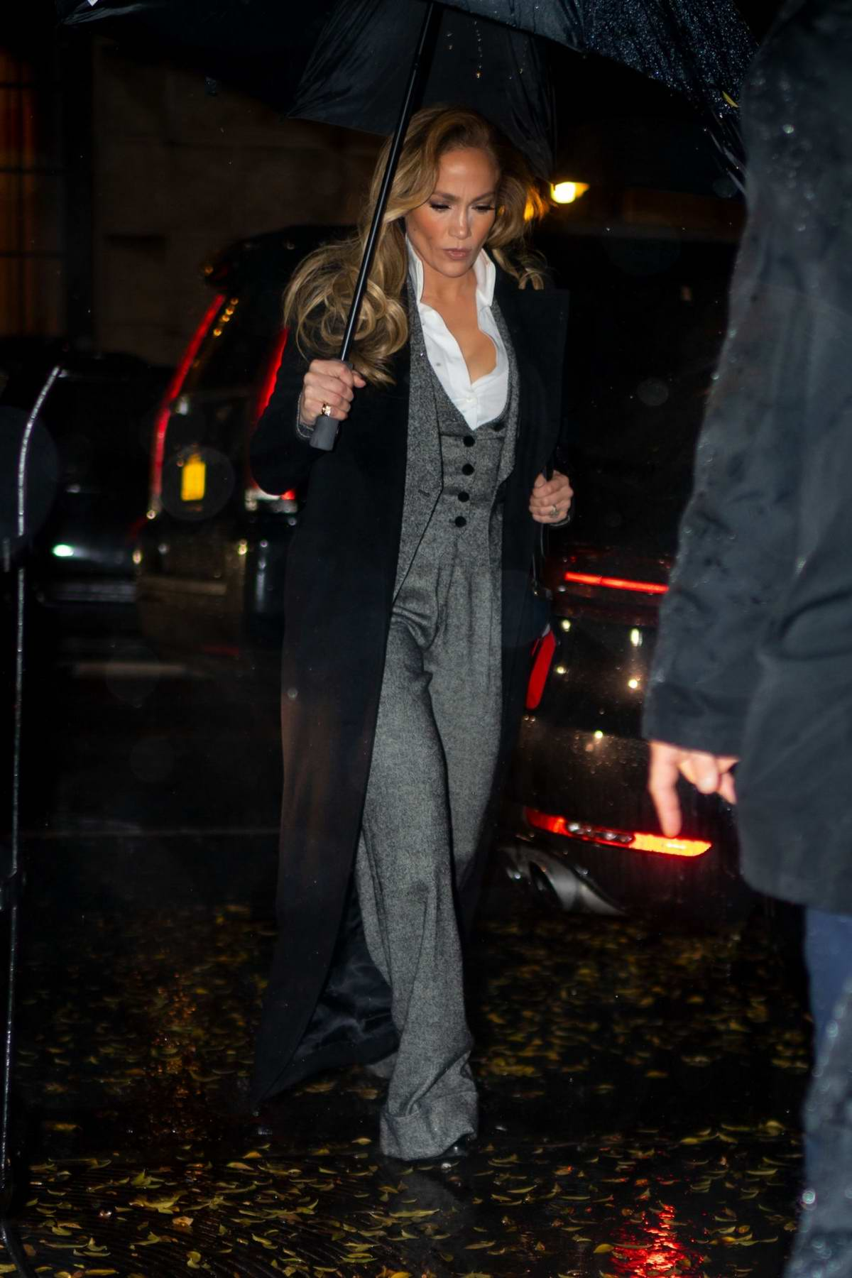 Jennifer Lopez looks stylish in a grey suit and black trench coat as she heads to dinner in New York City