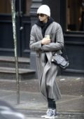Kaia Gerber wears a grey long coat, scarf, and beanie as she steps out in New York City