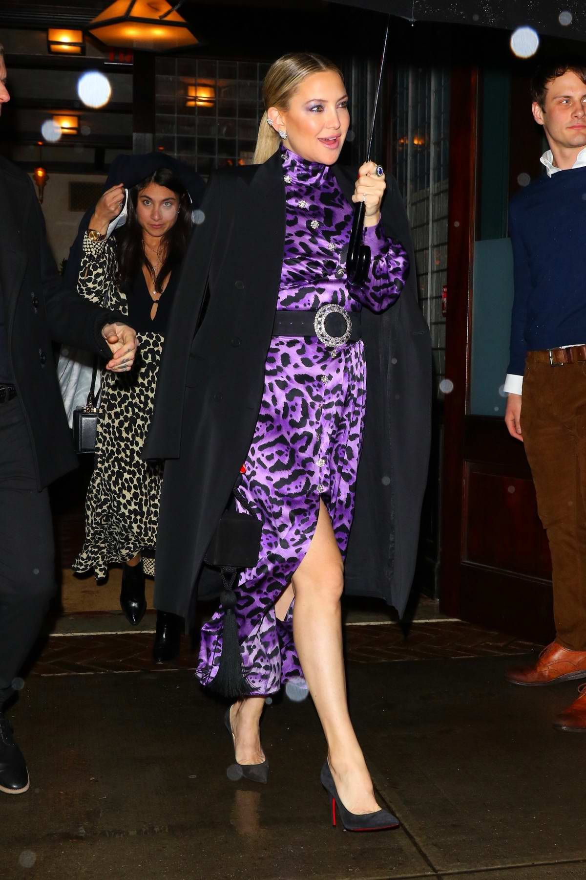 Kate Hudson braves the rain in a purple animal print dress as she leaves her hotel in New York City