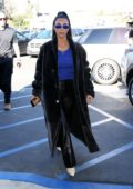 Kim Kardashian dons a black long coat with blue top and black leather pants as she heads to lunch in Calabasas, California