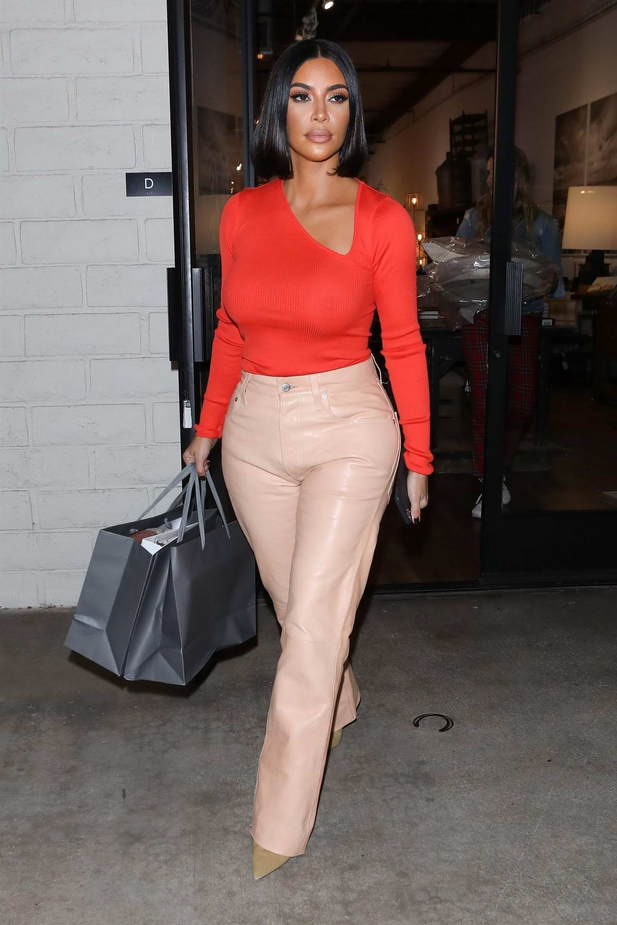 Kim Kardashian stands out in a bright orange top while out shopping at 'A Beautiful Mess' in Agoura Hills, California