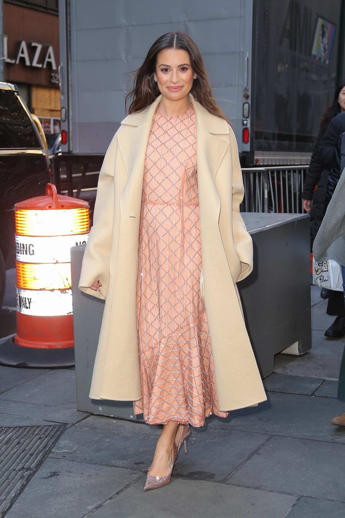Lea Michele looks great in a pink dress with beige trench coat while out in New York City