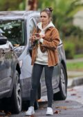 Lily Collins wears a hoodie paired with a brown jacket and leggings while out shopping in Los Angeles