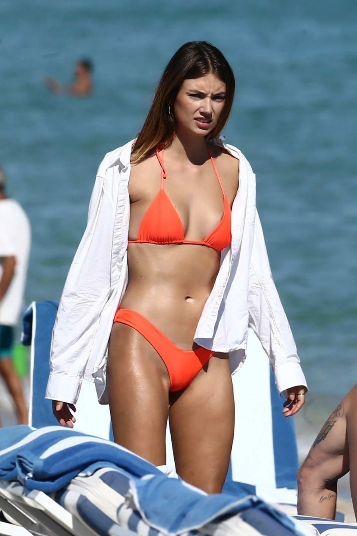 Lorena Rae sports a bright orange bikini as she hits the beach with friends in Miami Beach, Florida