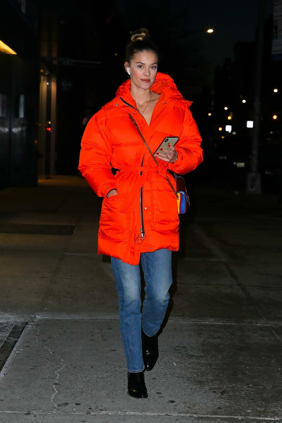 Nina Agdal looks striking in a bright orange jacket as she steps out in New York City