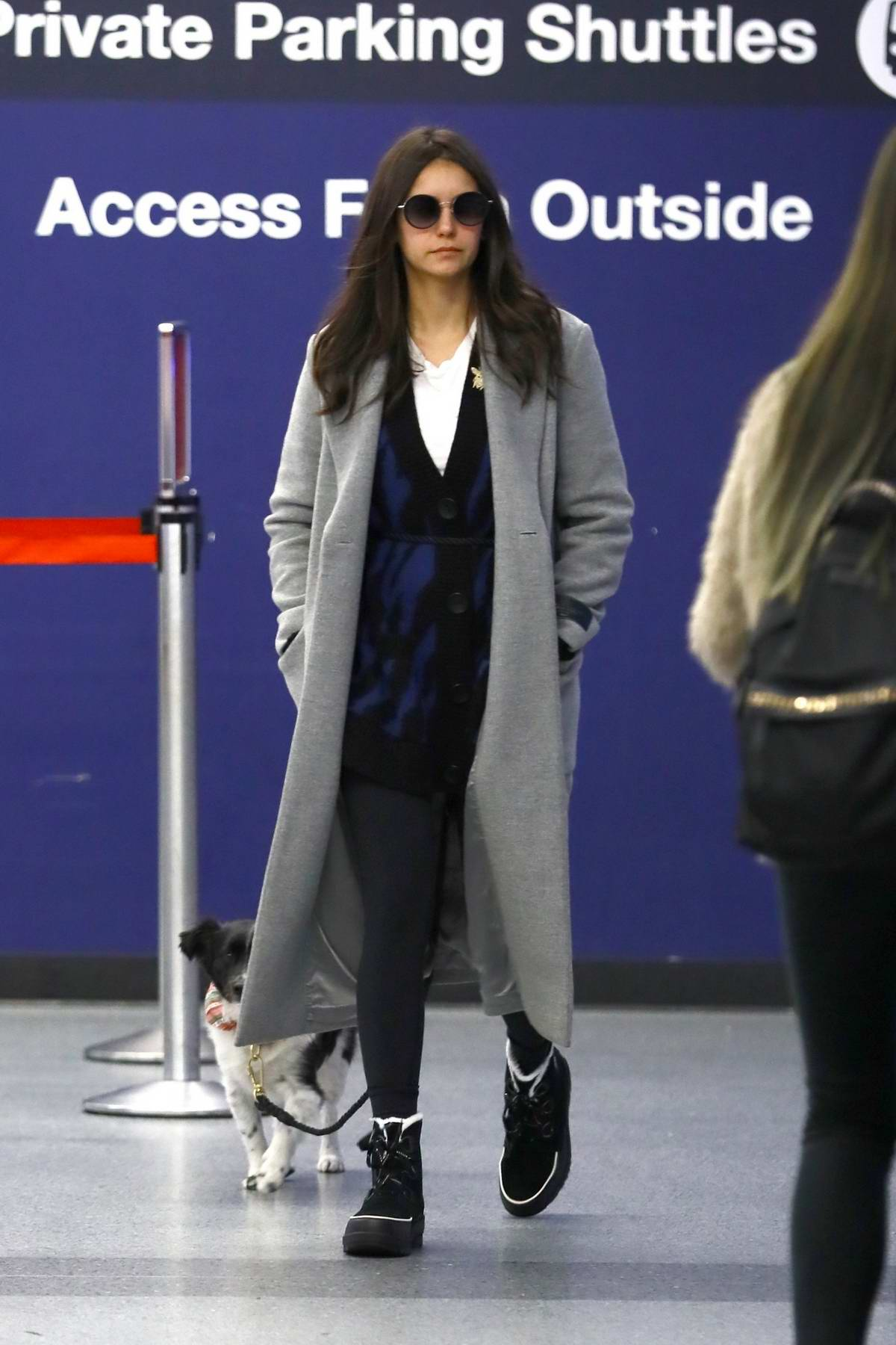 Nina Dobrev keeps it cozy in a grey long coat and leggings as she catches a flight out of LAX with her parents in Los Angeles
