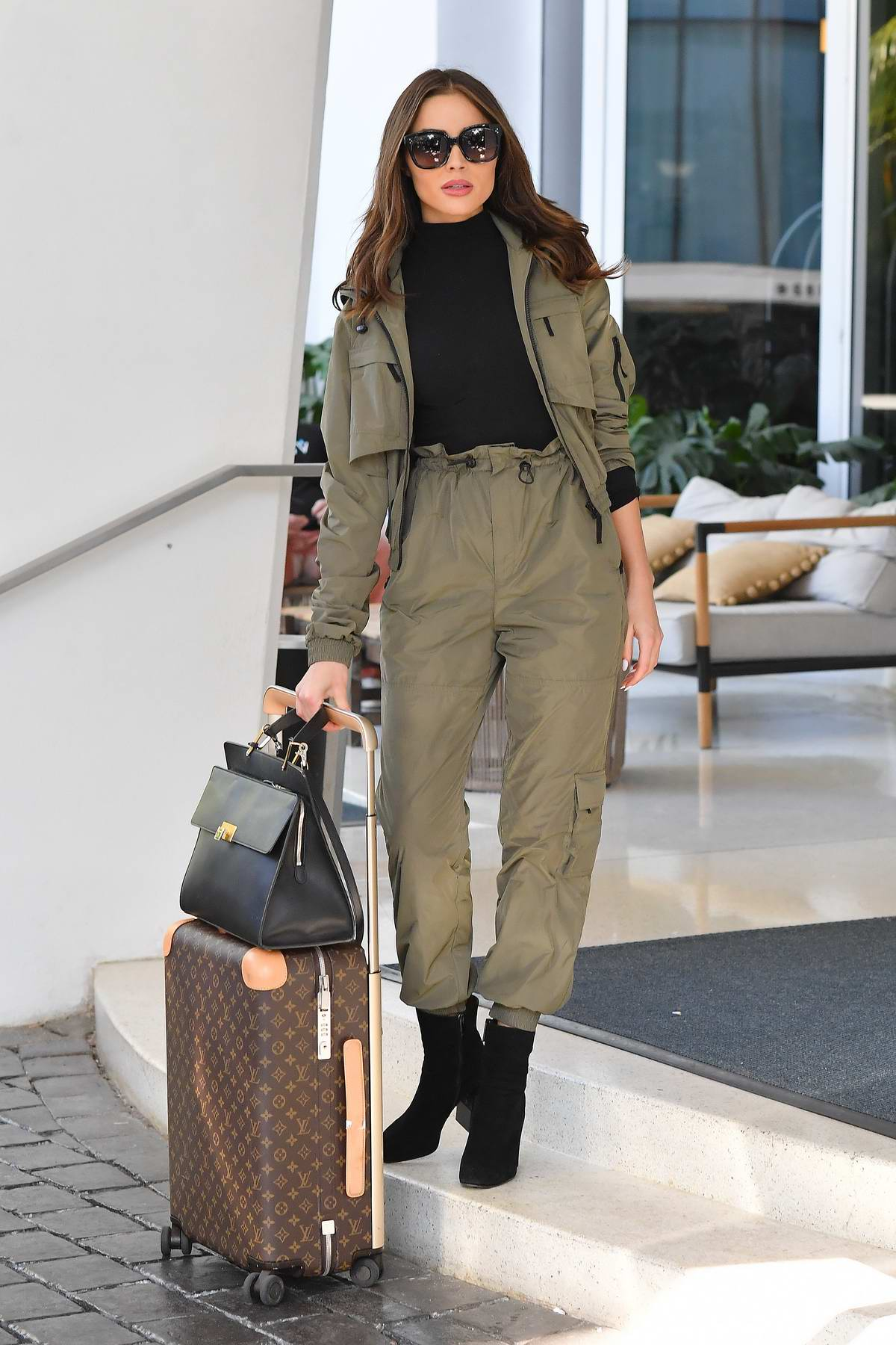 Olivia Culpo rocks an olive green jacket and matching pants as she leaves her hotel in Miami Beach, Florida