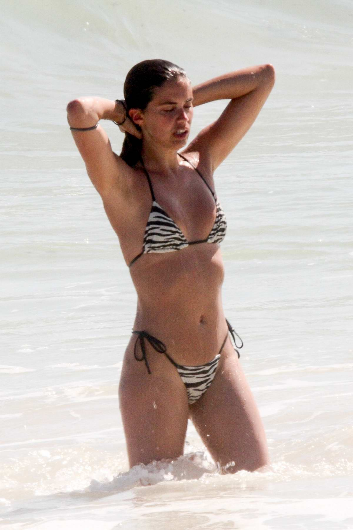 Sara Sampaio shows off her beach body in an animal print bikini as she enjoys the sun and the sea with Oliver Ripley in Tulum, Mexico