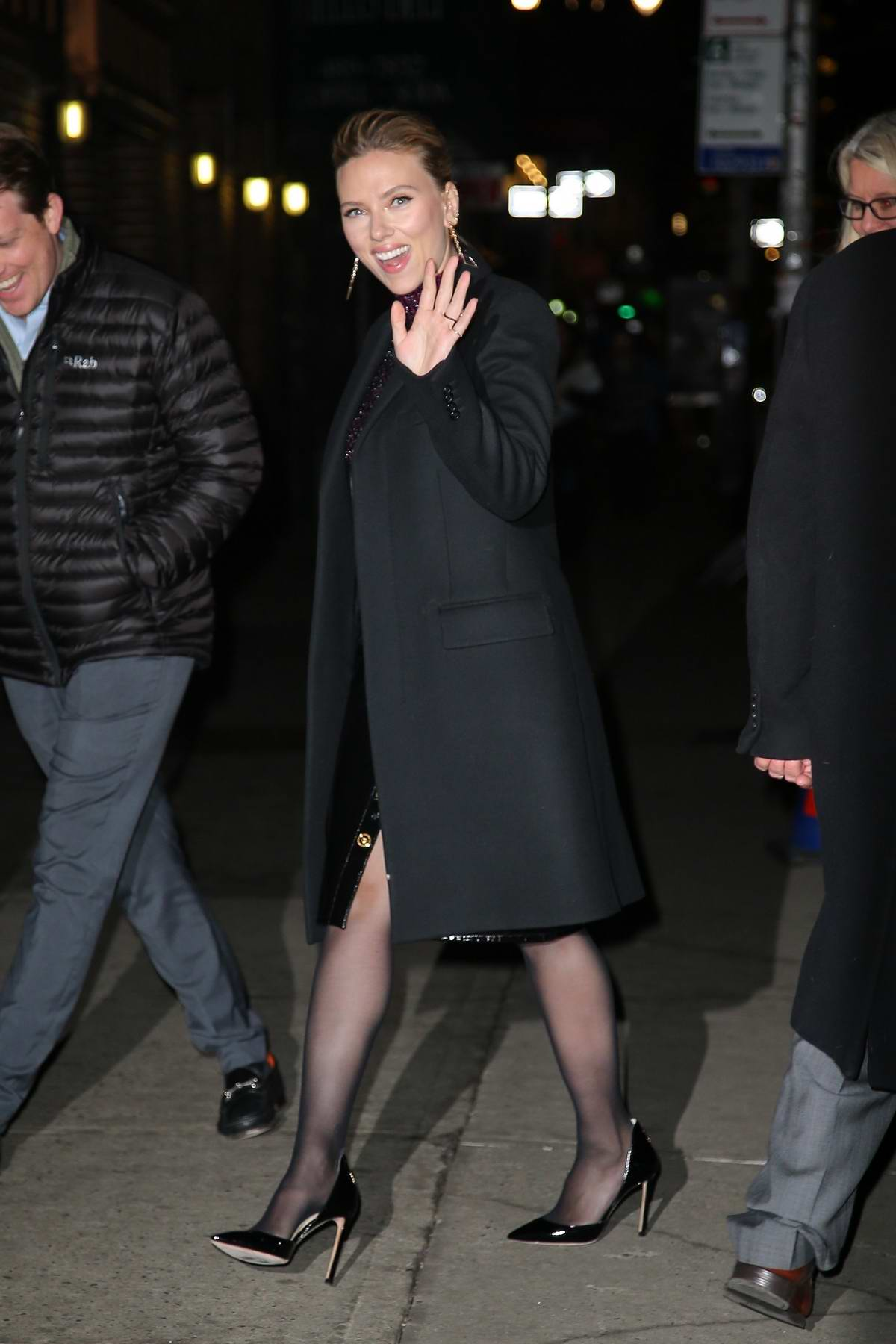Scarlett Johansson flashes a big smile and waves for the camera as she arrives at 'The Late Show With Stephen Colbert' in New York City