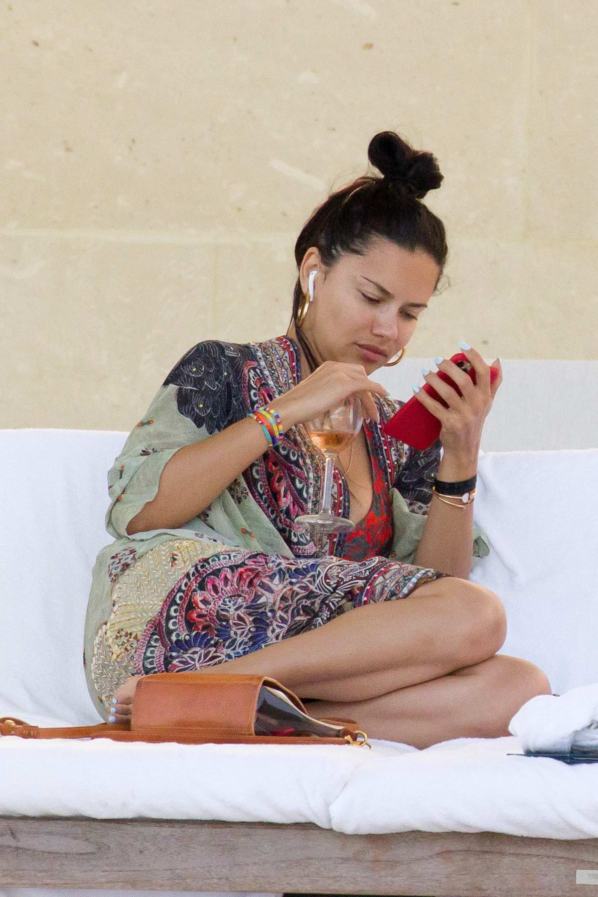 Adriana Lima spotted in a bikini as she lounges by the pool with her kids and friends in Miami, Florida