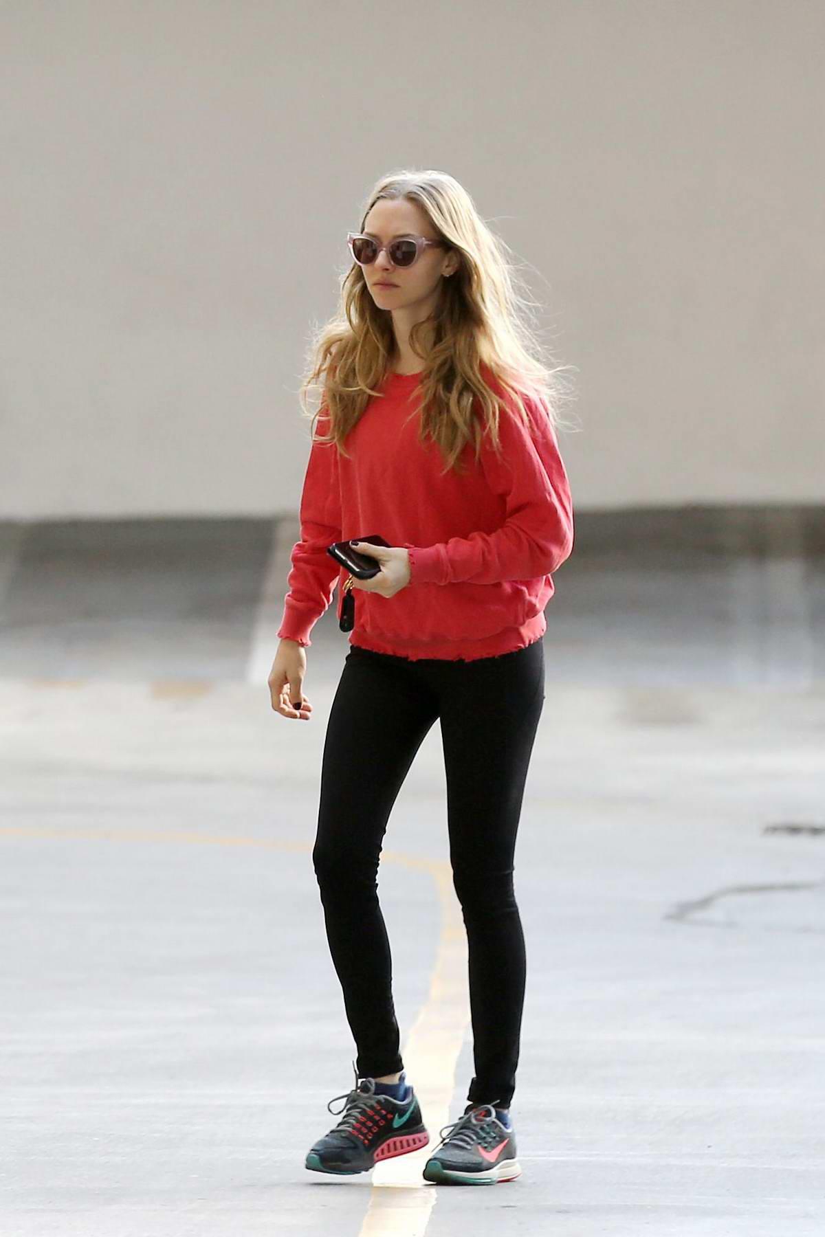 Amanda Seyfried wears red sweatshirt and black leggings as she stops by a FedEx Kinko's store in West Hollywood, California