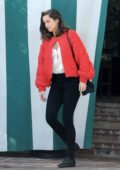 Ana de Armas seen wearing a red cardigan and black jeans while waiting for her ride in Los Angeles