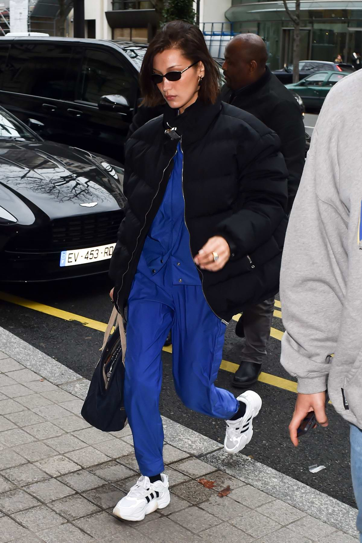 Bella Hadid rocks a blue jumpsuit with a black puffer jacket as she arrives for Paris Men's Fashion Week 2020 in Paris, France
