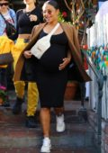 Christina Milian shows off her baby bump in a form-fitting black dress while out for lunch at The Ivy in West Hollywood, California