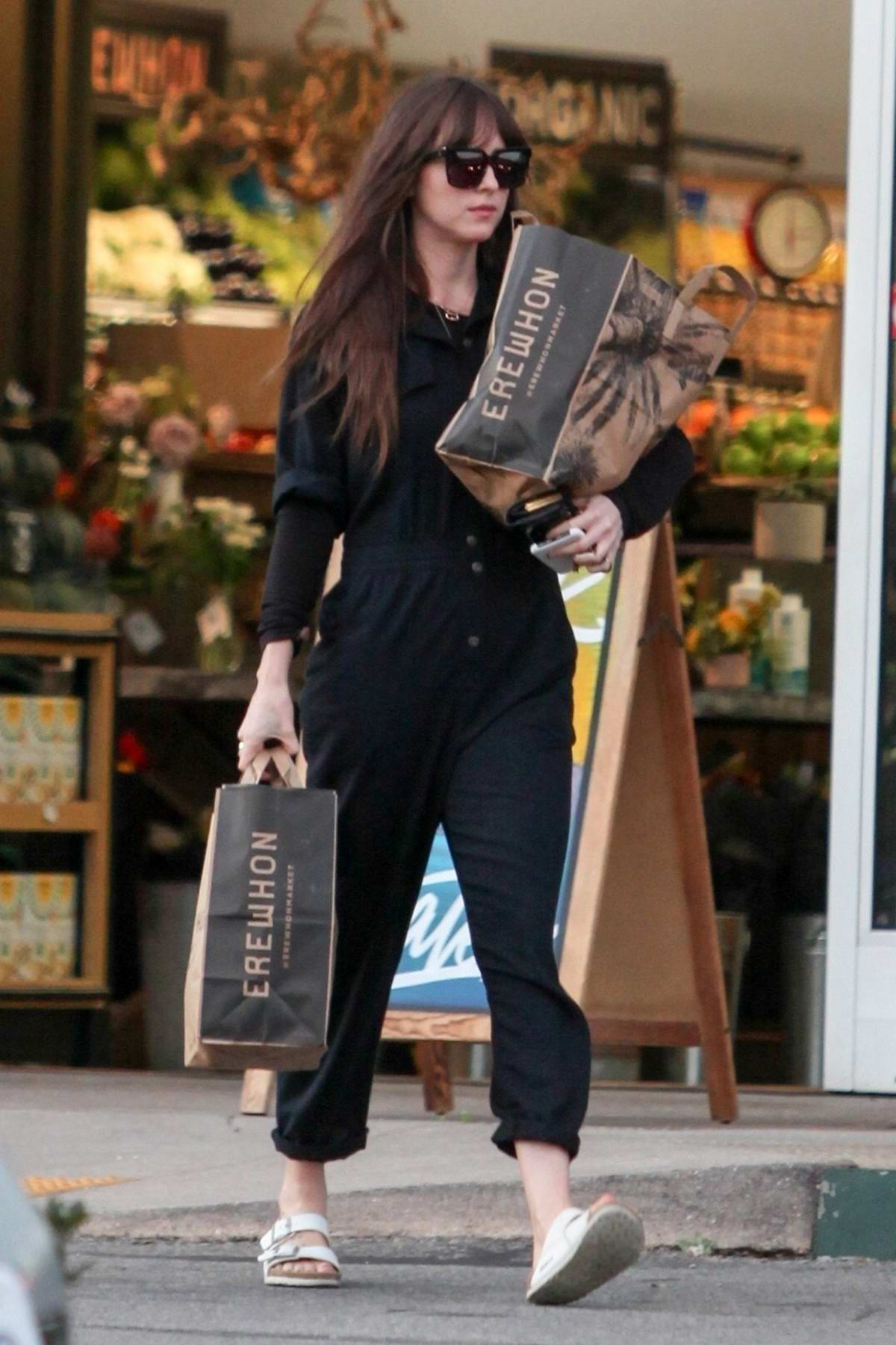 Dakota Johnson wears a black jumpsuit while grocery shopping at Erewhon market in Los Angeles