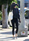 Dakota Johnson wears a dark grey sweatshirt and black leggings as she leaves the gym in Los Angeles