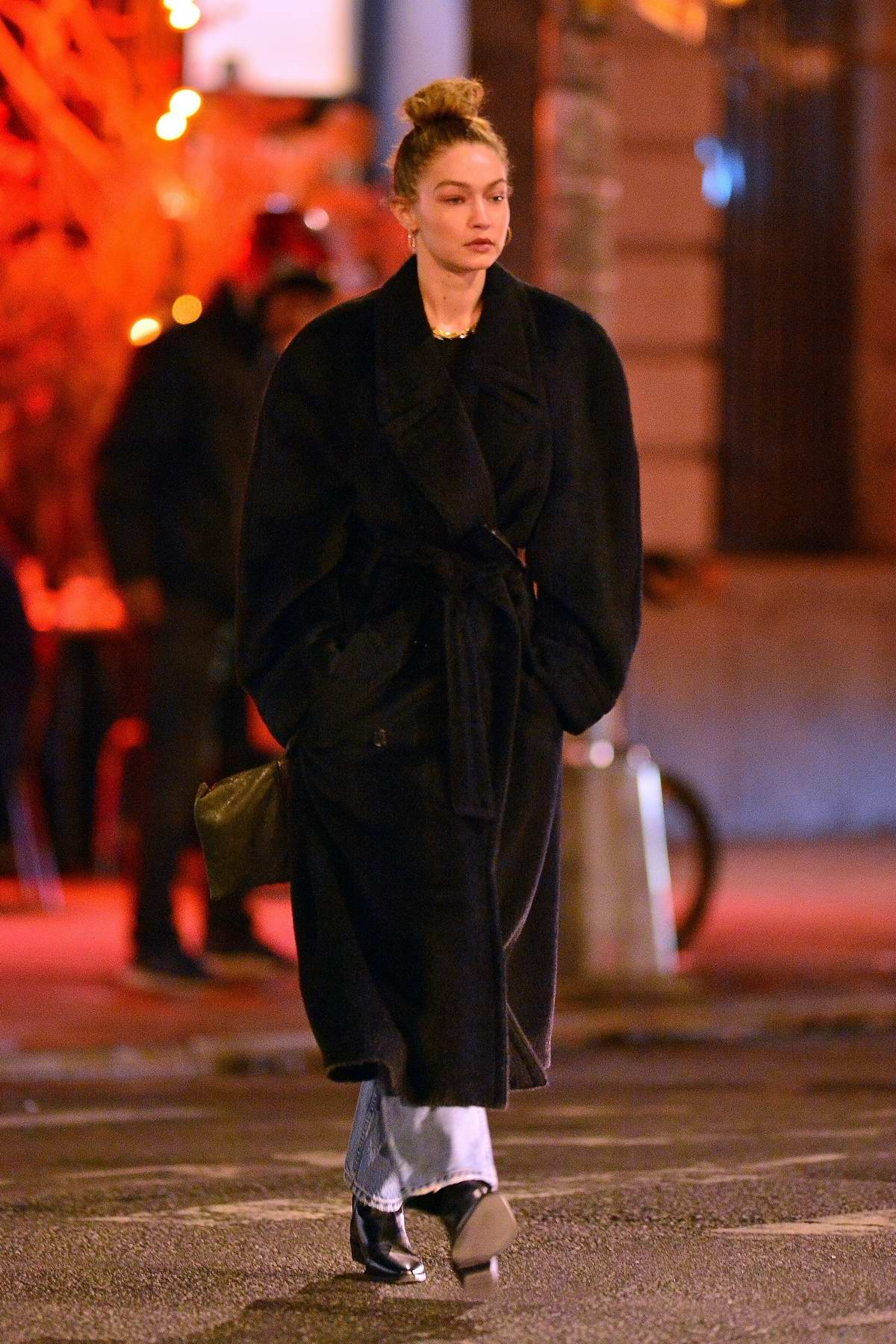 Gigi Hadid bundles up in a black long coat while out for a walk with friends in Soho, New York City