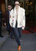 Gigi Hadid rocks bright orange boots as she steps out in Paris, France