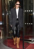 Gigi Hadid wears black leather pants with knee high suede boots as she leaves the Royal Monceau hotel in Paris, France