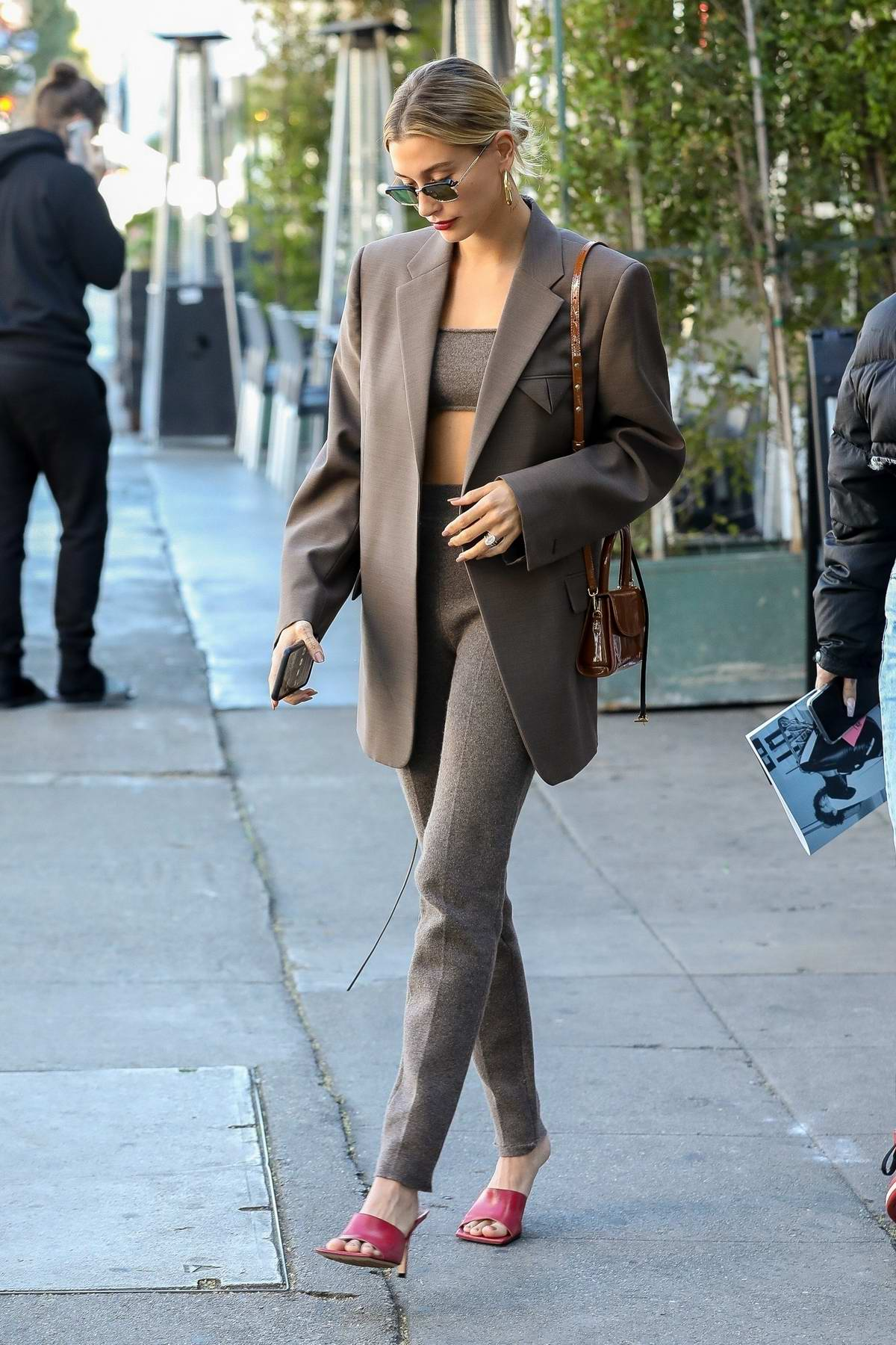 hailey bieber looks stylish in a brown suit and red shoes as