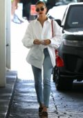 Hailey Bieber sports a white shirt and blue jeans while visiting a skincare clinic in Beverly Hills, California
