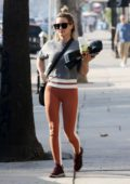 Hilary Duff looks toned in peach colored leggings and a crop top as she heads for a workout in Studio City, California