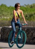 Kaia Gerber wears a green bikini top while out riding bikes with friends in Miami Beach, Florida