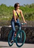 Kaia Gerber wears a green bikini top while out riding bikes with friends in Miami Beach, Florida