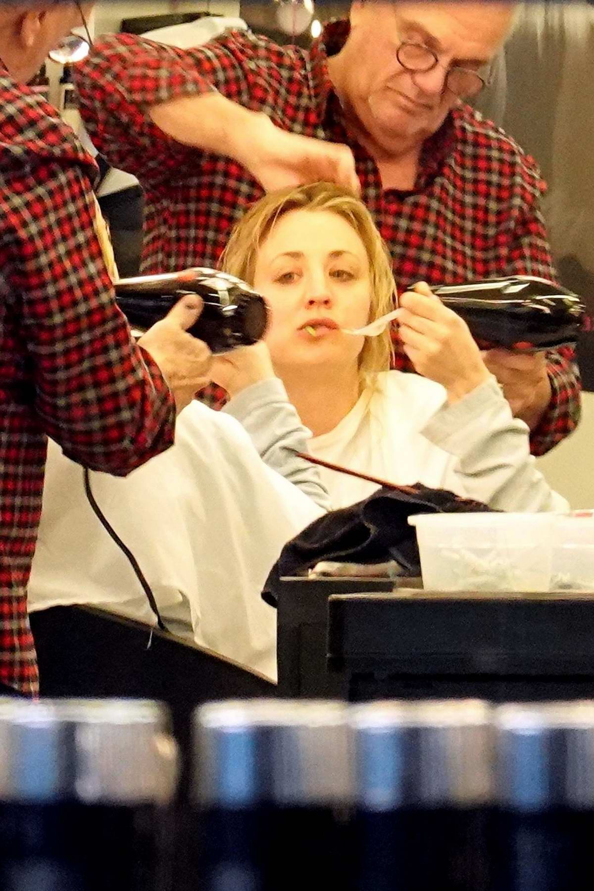 Kaley Cuoco chows down some food while she gets her hair done during her break in Rome, Italy