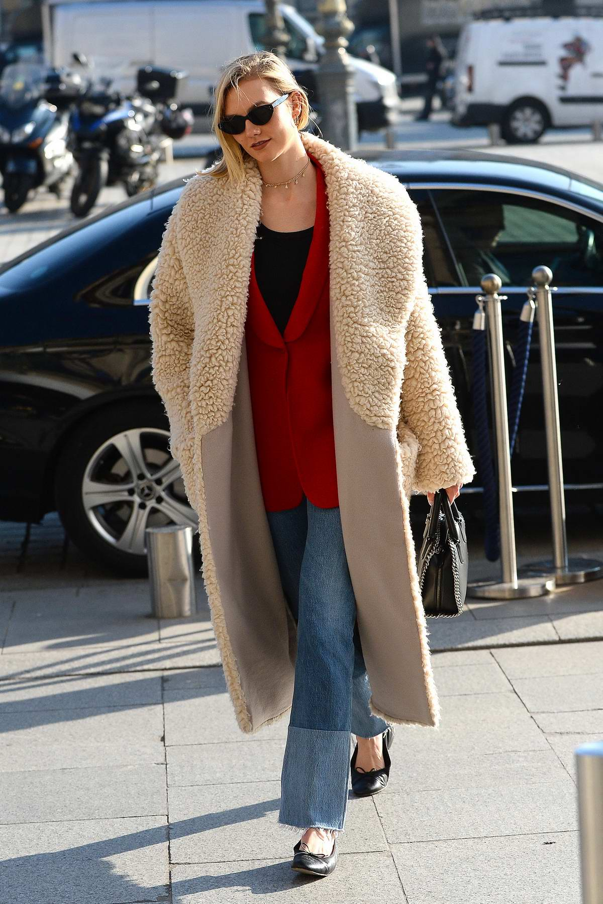 Karlie Kloss arrives all wrapped up in a sheepskin coat at the Ritz hotel in Paris, France