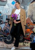 Karlie Kloss poses with a bouquet of flowers as she waits for her Uber ride outside a studio in Los Angeles