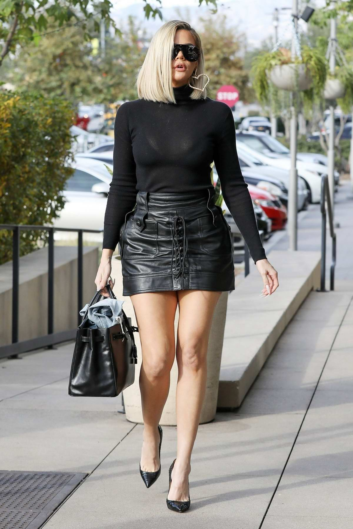 Khloe Kardashian rocks a black top and leather mini skirt as she arrives for a shoot at Villa in Woodland Hills, California