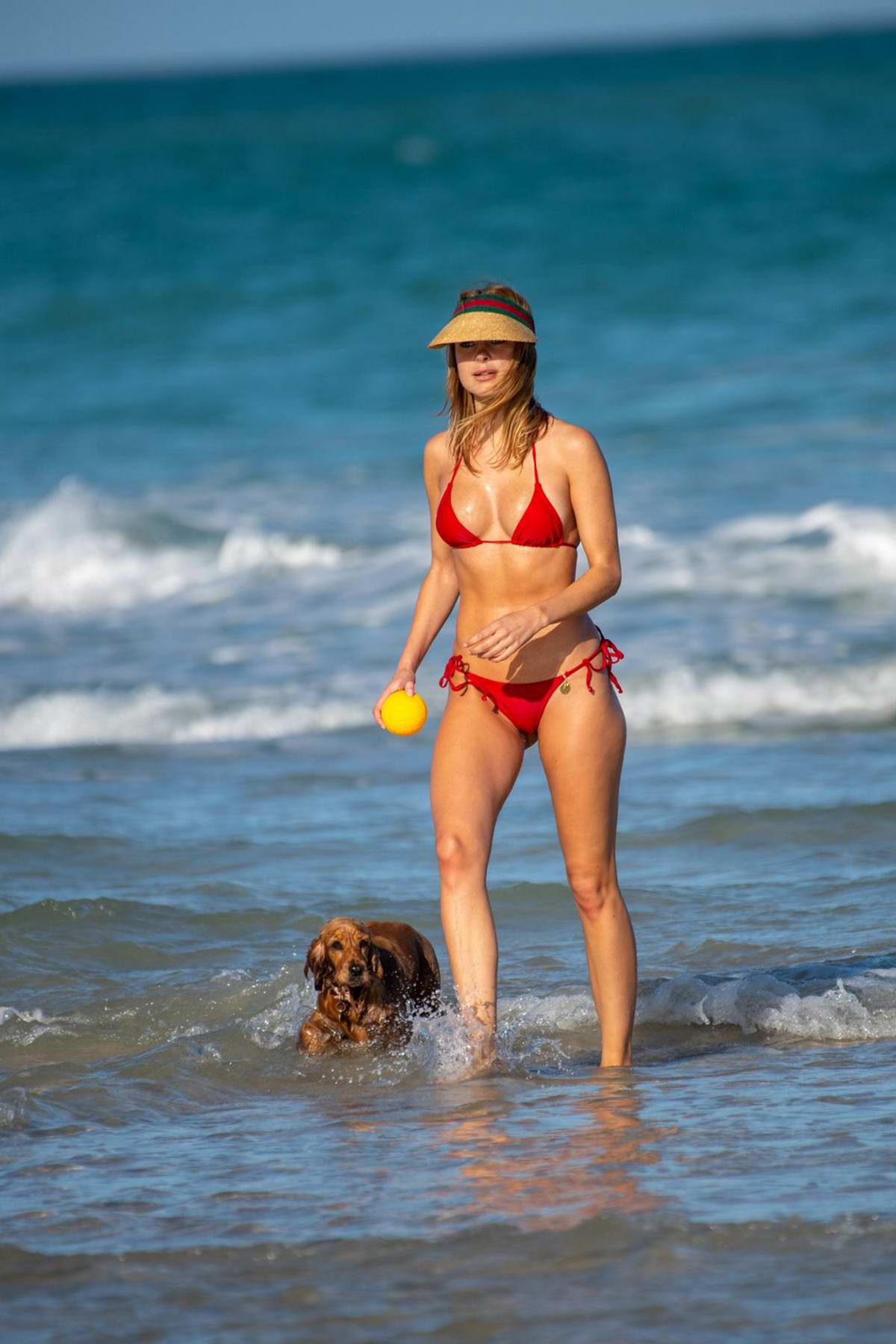 Kimberley Garner stuns in a red bikini while enjoying a day with her dog on the beach in Miami, Florida