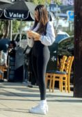 Madison Beer looks fab in a blue crop top and black leggings as she waits for her table at lunch in West Hollywood, California