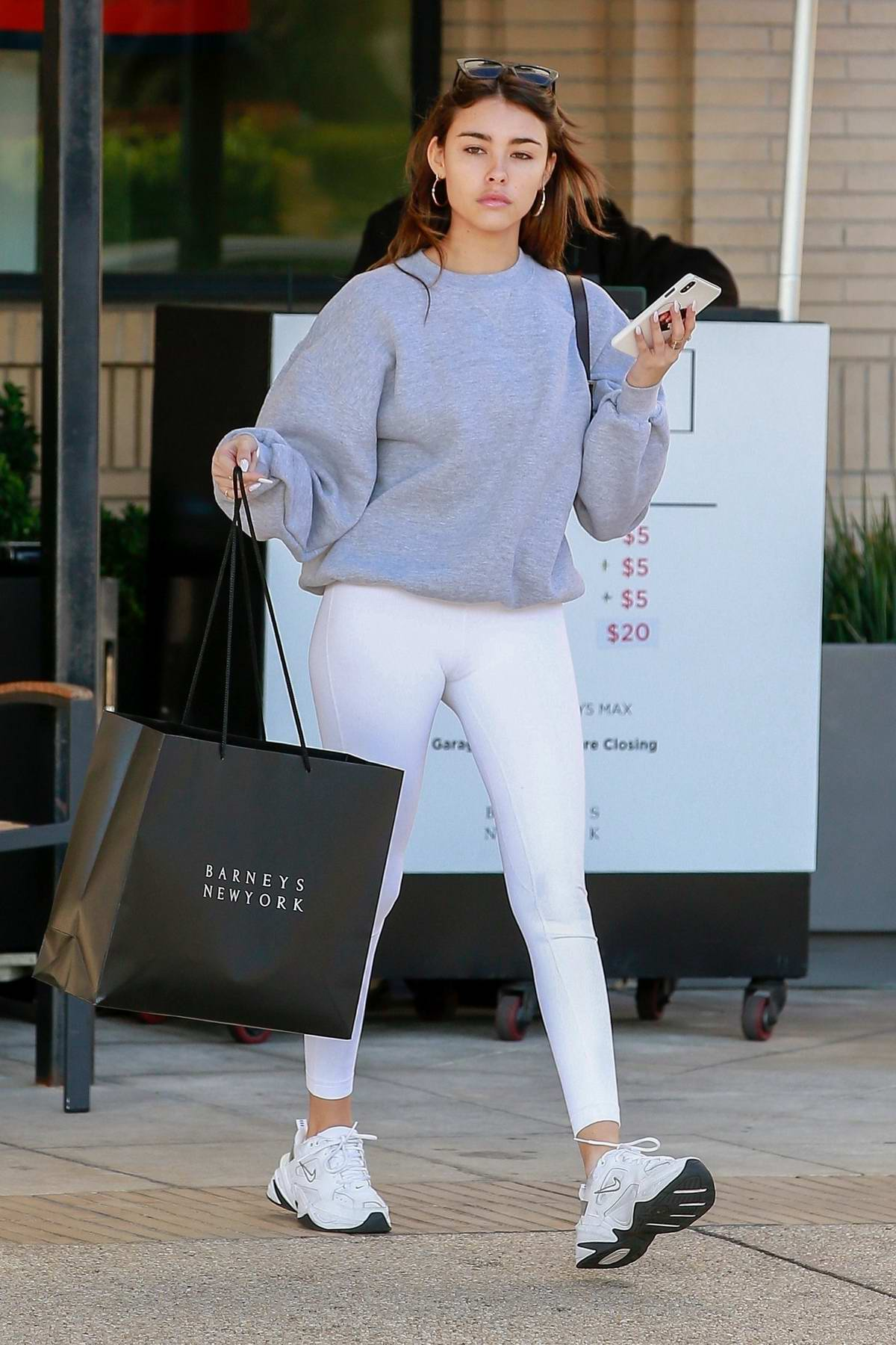 Madison Beer sports grey sweatshirt and white leggings during a trip to Barneys New York in Beverly Hills, California