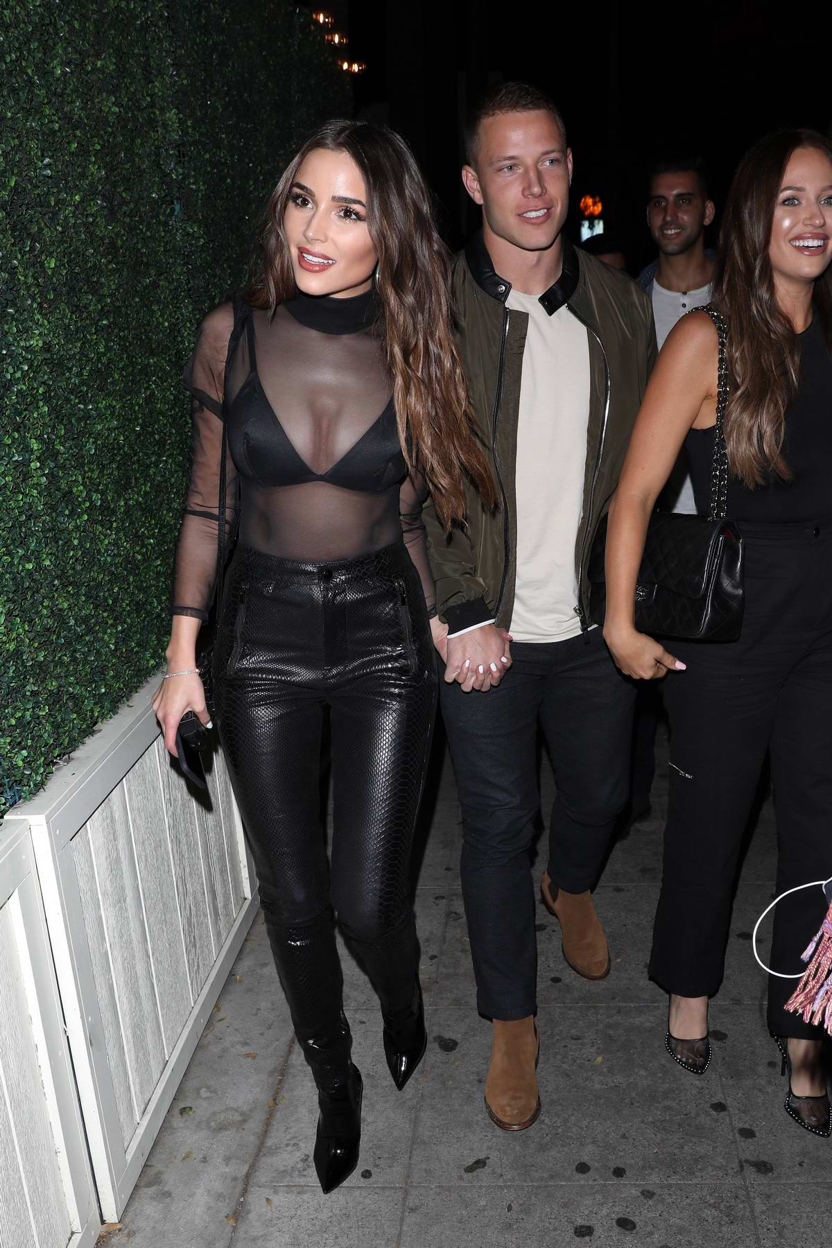 Olivia Culpo rocks a sheer top as she and boyfriend Christian McCaffrey head to the Delilah in West Hollywood, California