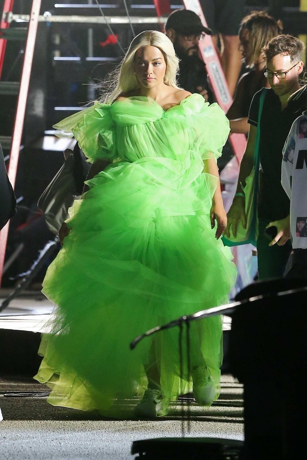 Rita Ora glows in a neon green dress shooting a Deichmann collection ad in Miami, Florida
