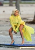 Rita Ora seen wearing a flowy yellow dress while shooting a music video on a windy day in Miami, Florida