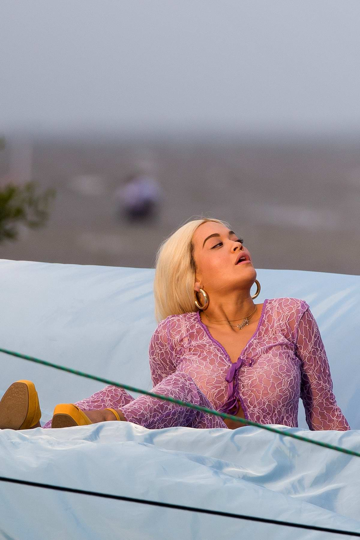Rita Ora wears a sheer pink outfit during a music video shoot in Miami, Florida