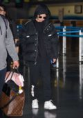 Selena Gomez keeps warm in a black puffer jacket, hoodie, and sweats while arriving at JFK Airport in New York City