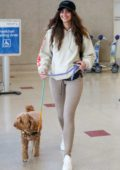 Taylor Hill looks cute in a hoodie and leggings as she arrives at LAX airport with her dog in Los Angeles