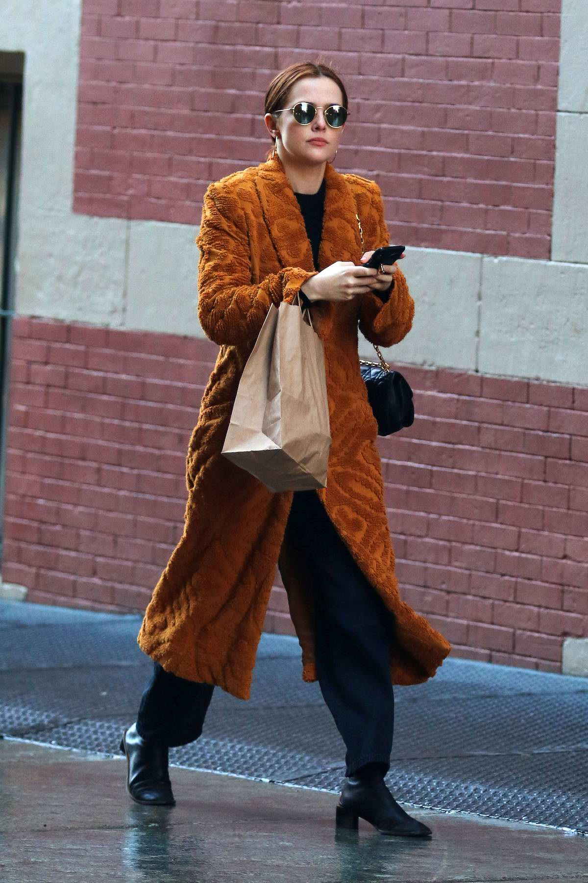 Zoey Deutch sports a rust colored coat while out shopping in SoHo, New York City