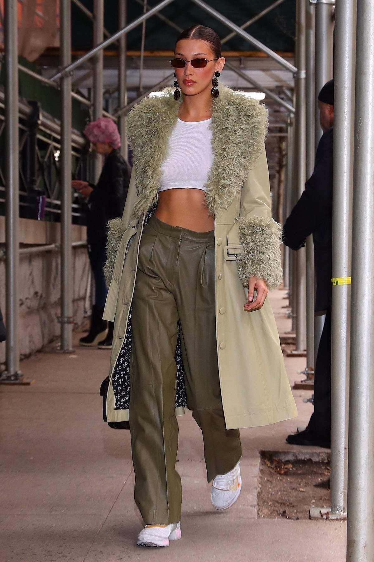Bella Hadid shows off her toned abs in a white crop top as she heads into the Marc Jacobs show in New York City