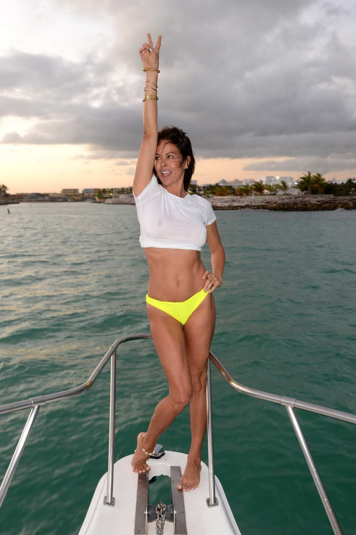 Brooke Burke wears a white crop top and yellow bikini bottoms while enjoying a day on a yacht in Dominican Republic
