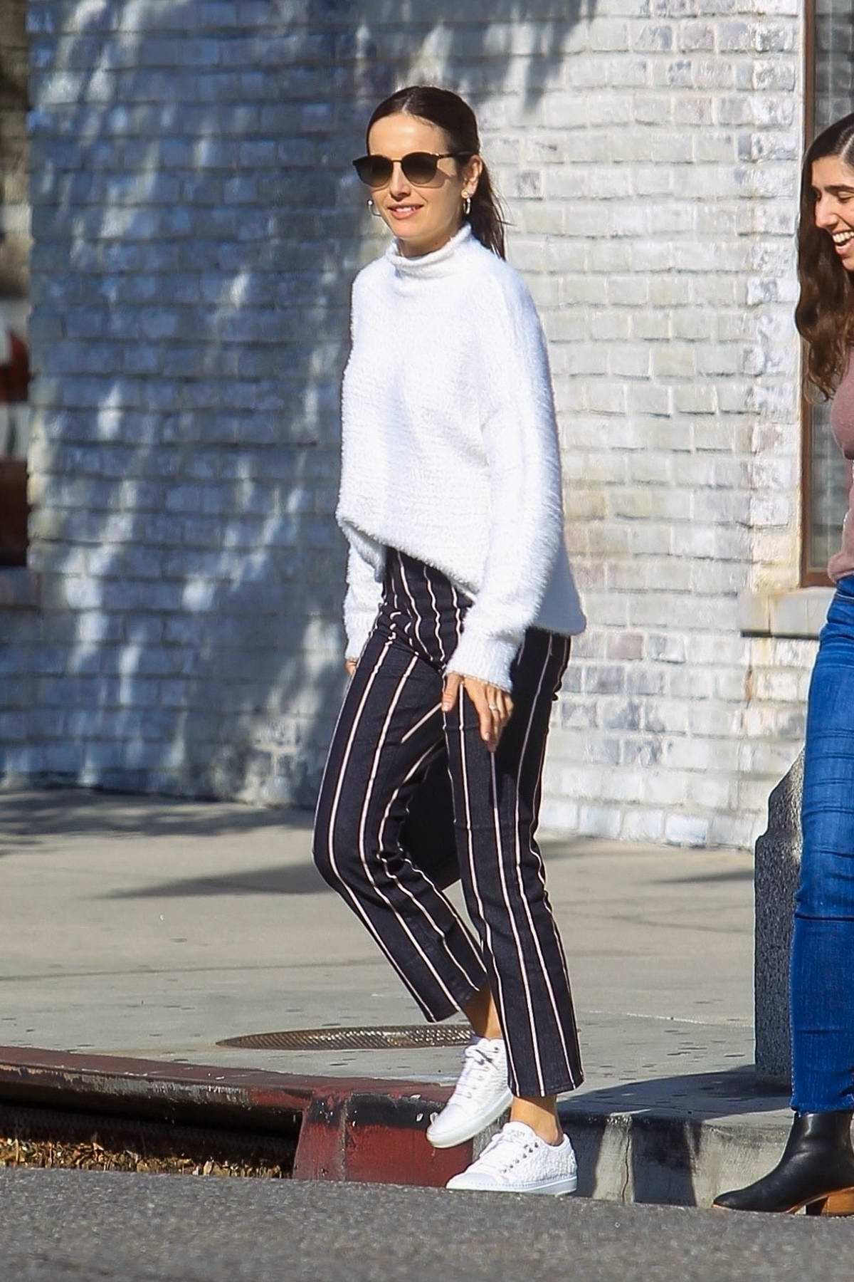Camilla Belle wears a white sweater and blue and white striped pants while out with a friend in West Hollywood, California