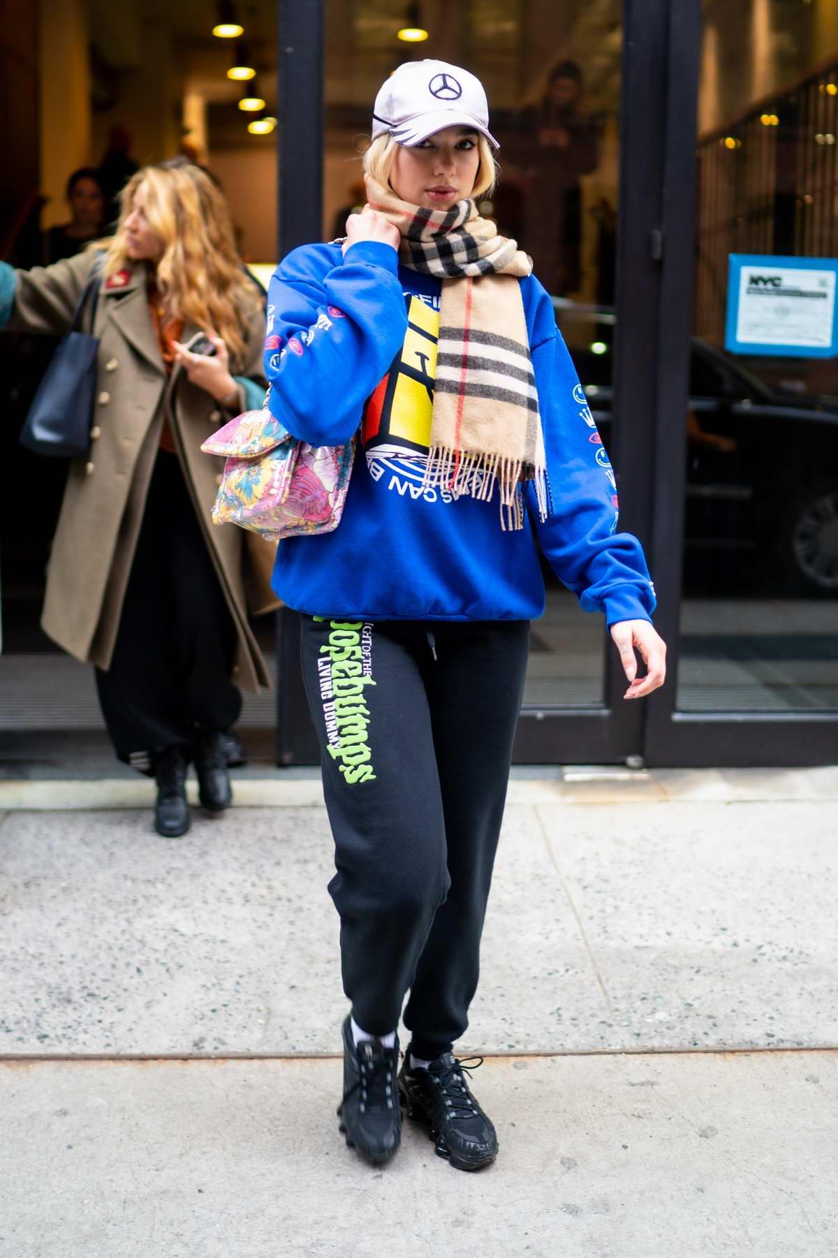 Dua Lipa seen wearing a bright blue sweatshirt as she leaves Milk Studios in New York City