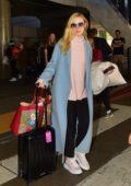 Elle Fanning carries a colorful Gucci bag as she touches down at LAX airport in Los Angeles