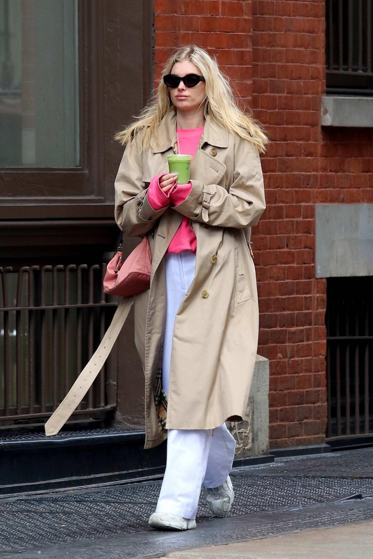 Elsa Hosk grabs a green smoothie as she steps out on a windy day in Manhattan, New York City